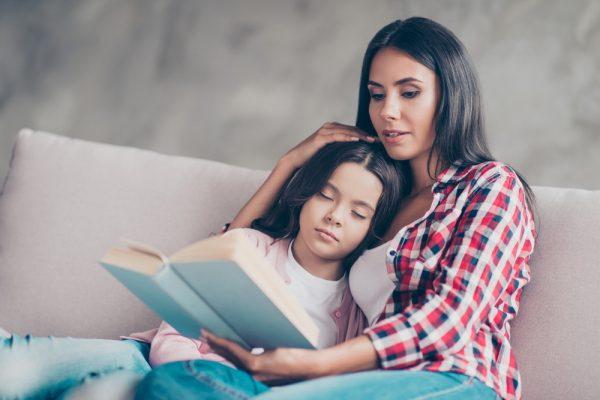 Девушка читает книгу ребенку
